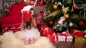 milagre : girl in New Years costume near Christmas tree with New Years surprise, Happy Christmas Vacation for younger sister, gift from Santa Claus for her daughter, plays with gifts in house, winter holiday