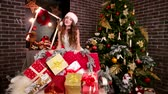 chimes : Beautiful girl in carnival costume with camera flirting playing, Santas joyful helper shows gifts, Near Christmas tree family gifts for New Year, Sister is preparing Christmas winter holidays