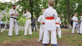carry out : Kherson, Ukraine - 27 May 2017: City Festival group children in kimono participate karate outdoors, trainer spend martial arts training into park, sport for kids in open air, slow motion