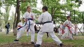 carry out : Kherson, Ukraine - 27 May 2017: City Festival boy and girl in kimono participate single fight, karate outdoors, martial arts training in park, sports for kids, fight children, slow motion