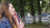 смаковать : woman pull hookah and talking on cell phone in parkland, beautiful girl holding shisha pipe outdoors, lovely female inhale taste tobacco on vacation, young women smoking hookah in open air Стоковые видеозаписи