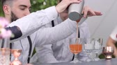 охлажденный : bartender fills wineglass with ice liqueur, barman uses mixing glass and strainer, barkeeper makes colour cocktail, tapster behind bar, making cocktail for customer, cafe on summer terrace