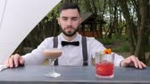 serves : portrait bartender behind bar, barmen submit alcohol, barkeeper close-up, colored chilled drinks on bar counter, beautifully decorated alcoholic cocktails with cube ice, slow motion Stock Footage