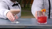 serves : barmen serves alcohol, close-up, barkeeper decorated colored drinks on bar counter, in hands bartenders chilled drinks, cocktails with cube ice on bartender desktop, slow motion Stock Footage