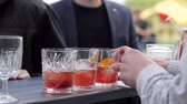 serves : barman makes beverage for client, barkeeper adds bit orange to drinking, hands bartender makes cocktail with ice, tapster standing at bar counter in on summer ground