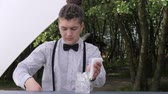 serves : bar worker pours ice cubes into an empty glass beaker, barman preparing cocktail, ice cubes mixing bar spoon, bartender makes mixed drink on background nature, man tapster for bar counter