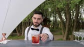 barkeeper : bartender shows gesture of approval, barkeeper thumb up, smiling barman serves liquor with ice on bar counter, bar worker gives cooling beverage on bar table, ready chilled cocktail summer restaurant