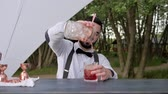 охлажденный : barman adds alcohol in juice with ice on bar counter, bartender prepares cooling cocktail with ice, barkeeper Makes alcoholic drink on fresh air, bar worker mixes alcohol for cocktail, event Service