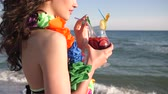 гавайский : Portrait of sexy girl on beach, summer vacation, women looking at sea ocean and drinking cocktail, Wind developing hair of happy young woman with Hawaiian Lei, expensive vacation on tropical islands, Стоковые видеозаписи