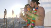 necklace : selfi guy and girl from beach an exotic resort, photo for memory from tropical islands, friends drink cocktail and take pictures on mobile phone, couple with flowers on neck photographed on gadget,