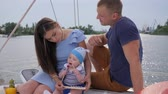 bue : young married couple with son resting on yacht, husband and consort with infant relaxes on pleasure boat, smiling men with wife and child on lake, teething at baby which bites toys outdoors in boat,