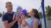 bue : woman entertains baby with help pinwheel on loch, weekend of male since spouse and kid on sailing yacht, child in hands of daddy near to mother on pleasure boat, dad and mom play with son at lake, Stock Footage