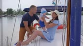 bue : travel young parents with little boy on river, holiday of happy couple with baby at sailing yacht in sea, portrait of happy family resting in boat on lake, family trip at loch in pleasure boat,