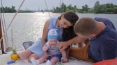 bue : nice married couple with kid relaxes on yacht, husband and consort with infant resting on pleasure boat, smiling men with wife and child on lake, teething at baby which bites toys outdoors in boat,