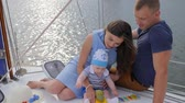 bue : husband and wife consort with infant resting on pleasure boat, smiling men with wife and child on lake, nice married couple with kid relaxes on yacht, teething at baby which bites toys outdoors in boat,