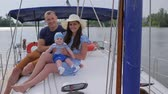 bue : holiday of happy couple with baby at sailing yacht in sea, portrait of happy family resting in boat on lake, family trip at loch in pleasure boat, travel young parents with little boy on river,
