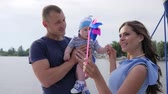 bue : dad and mom play with son at lake, woman entertains baby with help pinwheel, weekend of male since spouse and kid on sailing yacht, child in hands of daddy near to mother on pleasure boat,