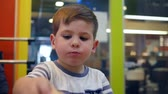 preguiçoso : Male child eats hamburger and French fries with sauce in fast food cafe, small boy eats with appetite in childrens restaurant, child eating food for dinner, French fries and burger for lunch schoolboy