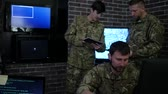 deneyimli : Two professional soldier in uniform, in military base, working for laptop, system tracking terrorists, briefing, on background multiple displays and group specialist discussing battle strategy