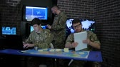 superior : soldier in camouflage uniform, view maps and working in laptoop, Military headquarters, briefing in monitoring room, discussing assault, security service and tracking terrorists, on background display screens Stock Footage