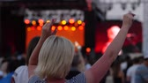 oditoryum : Dancing young girl in crowd of fans against backdrop of scene and bright flashing light close-up, Many fans at free rock concert in open air slow-motion, Huge number of happy spectators at concert,