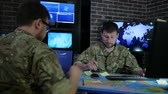 deneyimli : pro officer men in camouflage uniform, in system control center, working for laptop, briefing military IT technicians, discussing battle strategy, on background multiple displays and world map Stok Video