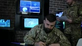 zkušený : portrait warrior guy in form, in field headquarters, Cyber war strategy, attack security virus infection, satellite surveillance monitor screen, on background monitor and employees