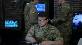 commander : portrait serious soldier in uniform, in military headquarters, cyberterrorism and searches safety system, briefing military IT technicians, on background multiple displays and specialist Stock Footage