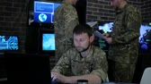 commander : portrait proficient soldier, in military base, working for laptop, system tracking terrorists, briefing, on background multiple displays and group specialist discussing battle strategy