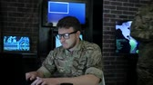 командир : portrait pro soldier in glasses, in control room, working for laptop, search safety system, briefing specialists, on background multiple displays and group people discussing battle strategy