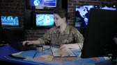 commander : portrait experienced officer woman in camouflage uniform, in military base, War center, working for laptop, system tracking terrorists, briefing, on background multiple displays and world map