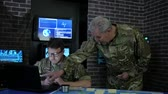 sálvia : chief and soldier in camouflage uniform, at briefing, in monitoring room, view maps, discussing assault, security service and tracking terrorists, on background display screens Vídeos