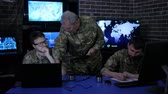 recon : security service, commander in uniform in monitoring room on war base, group military IT professionals manages station, people beside computer and monitor screen, military control