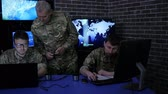 recon : officer in uniform in monitoring room on war base, group military IT professionals manages station, people beside computer and monitor screen, military control, security service