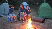 kids tent : travel in camp, mother and two children sitting around on straw bale beside balefire, mom and kids communicate near bonfire, young family in background tents and trees, family weekend in forest