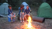 kids tent : family weekend in forest, mom and kids communicate near bonfire, young family in background tents and trees, mother and two children sitting around on straw bale beside balefire Stock Footage