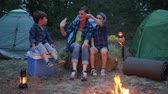 kids tent : happy family on vacation outdoors, mother and two children sitting around on straw bale beside balefire, mom and kids communicate near bonfire, family enjoying camping in forest Stock Footage