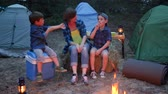 kids tent : family enjoying camping in forest, mother and two children sitting around on straw bale beside balefire, mom and kids communicate near bonfire, young family on vacation outdoors