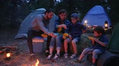atividades de fim de semana : family eating corn from out fire, travel camping, picnic in forest, mama, daddy and sons eat fresh yellow maize at night in open air, journey with tents during summer holidays Vídeos