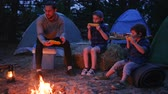 kids tent : daddy with sons eat up fresh yellow maize from out fire during summer holidays, dinner in evening near flames on nature, family enjoying corn with salt, picnic on outdoors