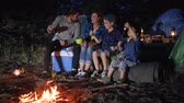 toasting : husband and wife with kids puts zephyr to skewer near campfire in woodland, family communicates and putting marshmallows on skewer near fire in forest, parent with children enjoying camping on nature, Stock Footage