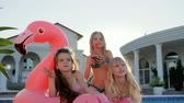 mít : kids celebrities in swimsuit on summer vacation, little girls lie on inflatable pink flamingo near pool, spoiled rich childs in backlight, children have fun in background villa