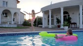 детский : sweet child in Inflatable ring swim in pool In sunlight, Little girl In bathing suit dancing by Swimming-pool, happy childhood of Children of Rich parents, Expensive weekend of sisters At villa,