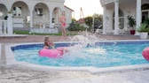 konak : Little girl swimming on Inflatable ring and Gives of Water splashes in Poolside, Rich Small Sisters spend summer in mansion In pool, Beautiful Children of celebrity rest in Poolside, Stok Video