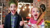 coringa : harley quinn and joker screaming, kids having fun at halloween party, crazy characters, spooky makeup, children killers halloween costumes, baseball bat, masquerade at all saints day, trick or treat