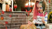 grimasa : harley quinn decorating pumpkin with sweets, halloween costume, dangerous child, halloween party decorations, crazy character, masquerade at all saints day, time for trick or treat, autumn holiday Dostupné videozáznamy