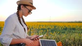 коллектор : producing energy, girl communicates in social network using mobile and solar panel on background field, young woman browsing cellular phone uses solar battery, female with cellphone and battery Стоковые видеозаписи