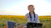 innovative technology : ecology, young woman shows symbol of approval using solar panels outdoors, female in backlight with notebook charger, girl near solar battery and laptop on field of sunflowers Stock Footage