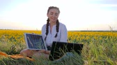 gerar : clean energy, young woman talking on laptop using solar panels outdoors, female in backlight with notebook charger from sun, girl holds in hand solar battery on field of sunflowers