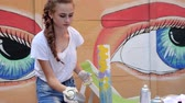 camiseta : design clothes of handmade outdoors, beautiful girl with cans of paint in hand, White t-shirts painting in street style, young womans Painted clothes with spray paint on background of graffiti,